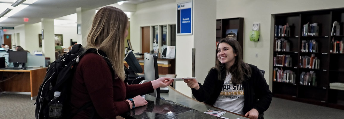 Smiling student worker at Library Service Desk